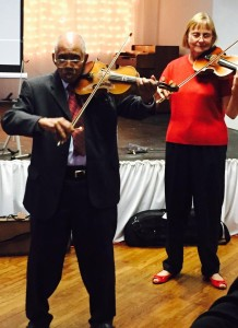 Dr J playing his violin for his guests.